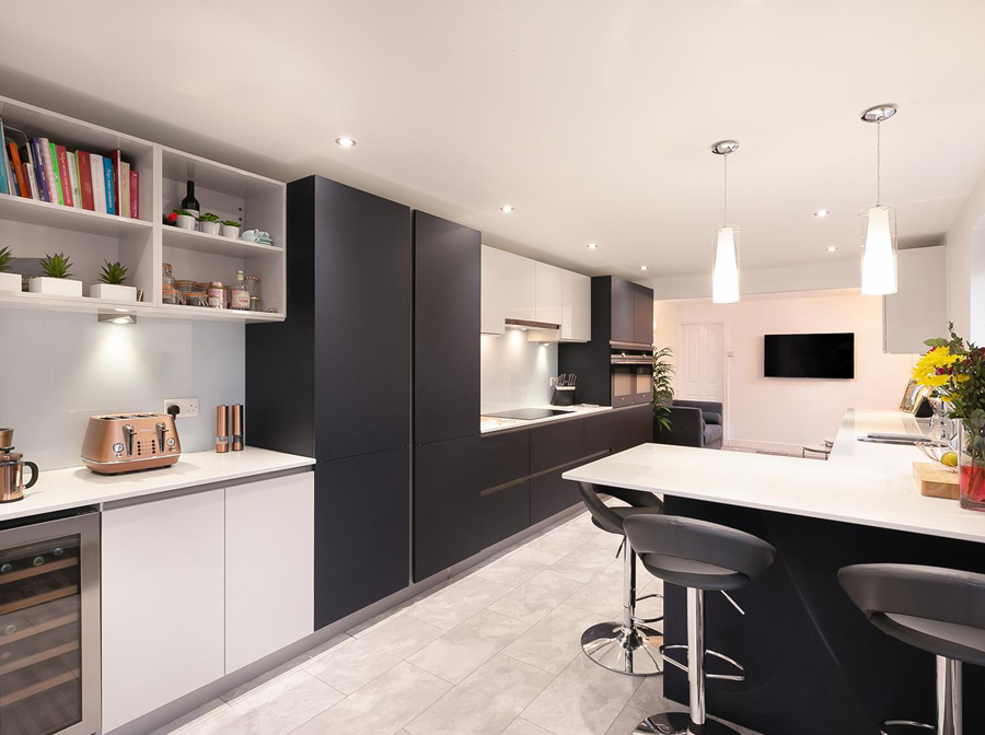 Matt midnight blue modern kitchen with quartz worktop and glass splashback – Urmston