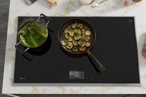 Image of an induction hob with a pot and pan cooking food.)