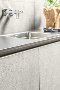 A close-up image of a modern kitchen sink with wall-mounted taps in this modern kitchen design