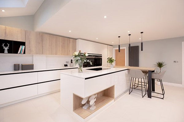 Image of an all-white handleless kitchen design featuring natural wood accents, a white kitchen island, and spotlights.)